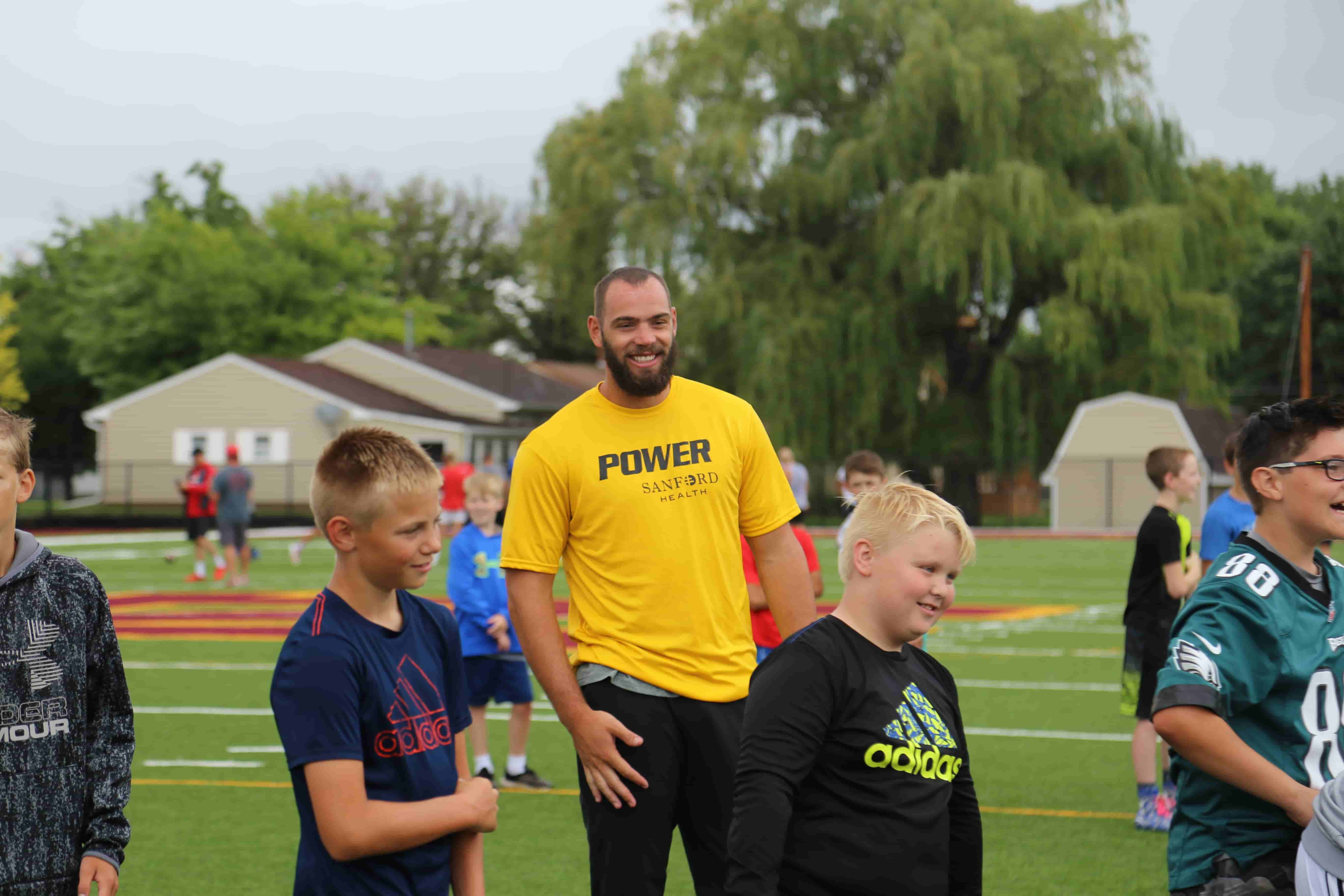 NFL player standing with kids at football practice field