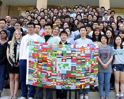 A crowd of business students displays an international flag