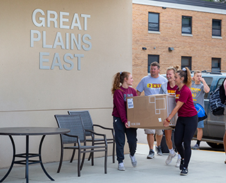 Students carry a large box into Great Plains East