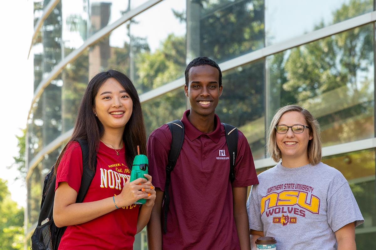 Three students stand smiling in front of the Technology Center