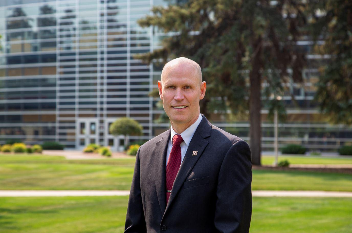 NSU  President Neal H. Schnoor, wearing a dark suit and maroon tie, stands on the campus green with the Tech Center in the background.