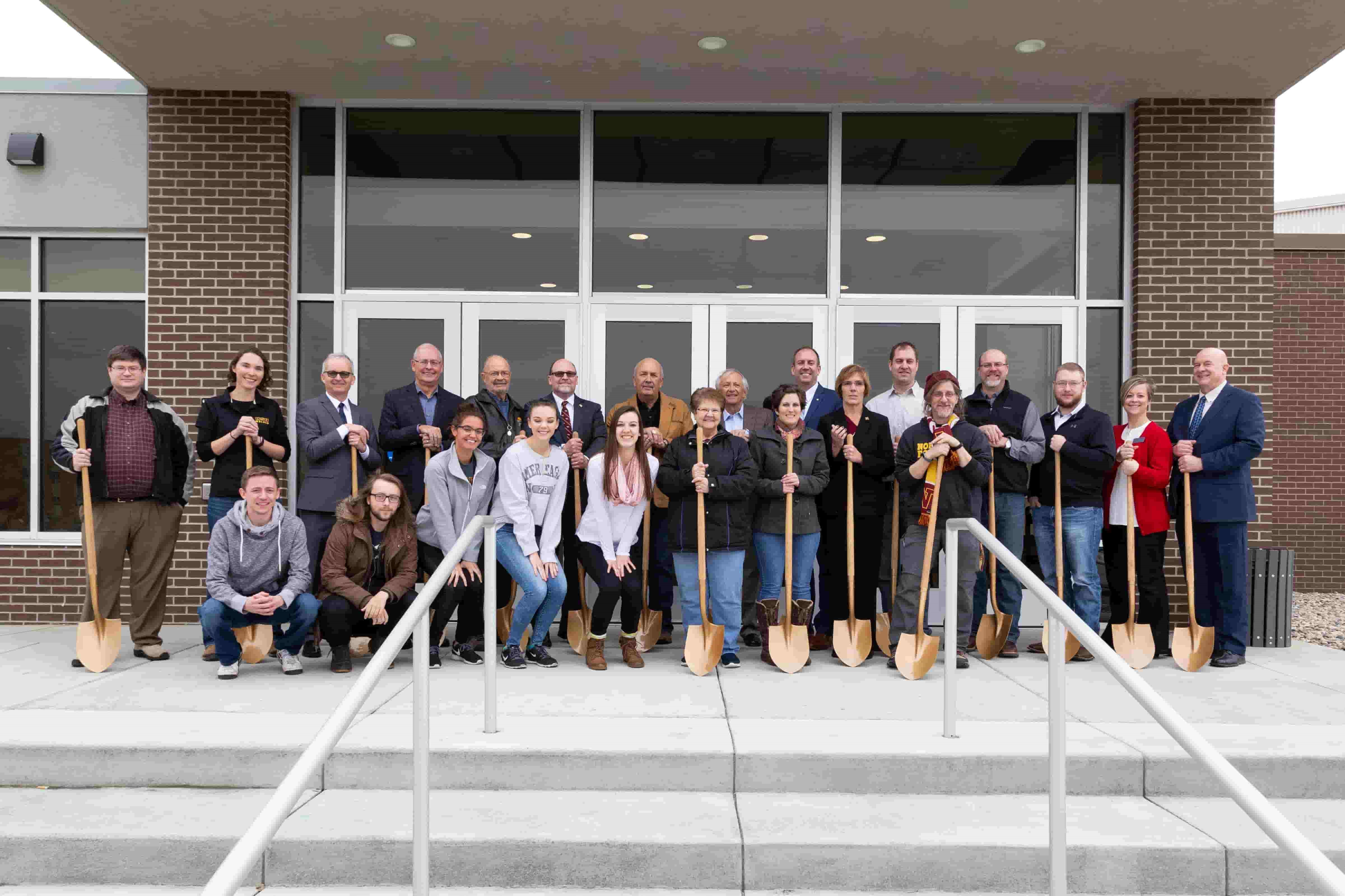Group photo of faculty and students with shovels
