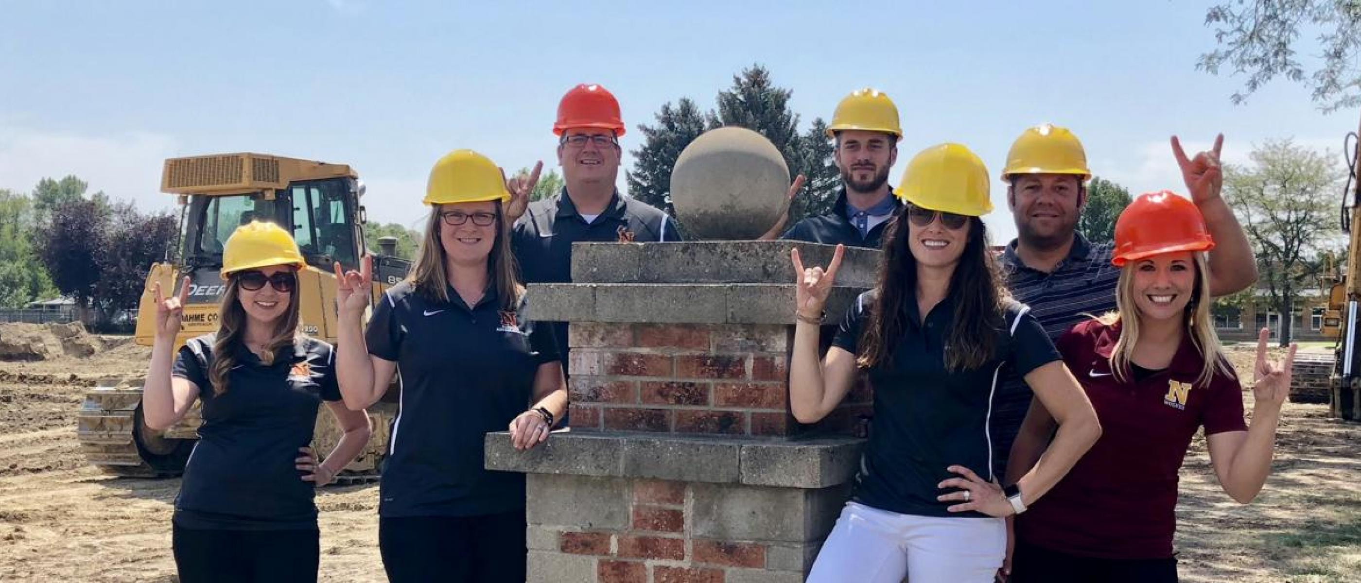 Alumni pose next to an NSU column by a campus construction site