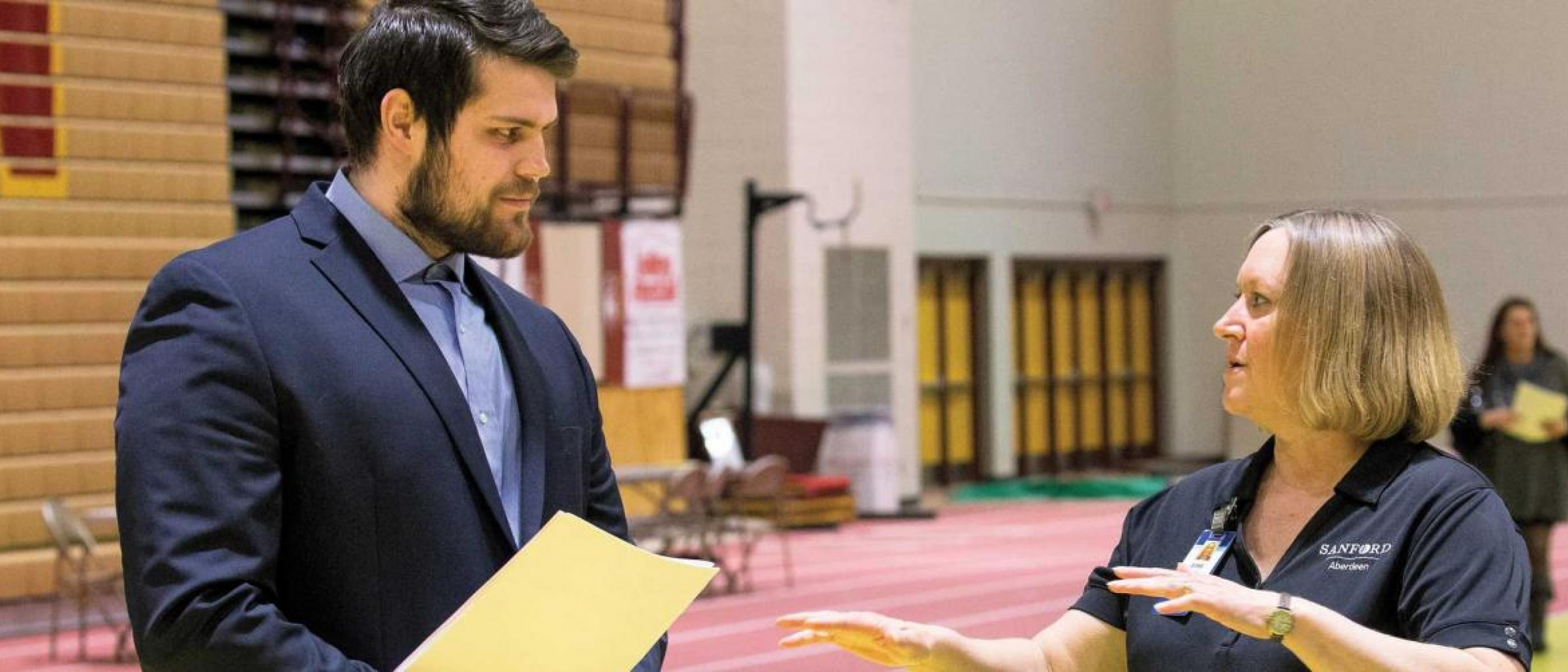 Student holding file talking to employer in athletic arena