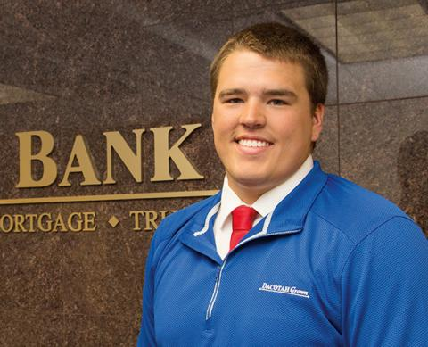 Smiling male graduate standing in front of Dacotah Bank sign