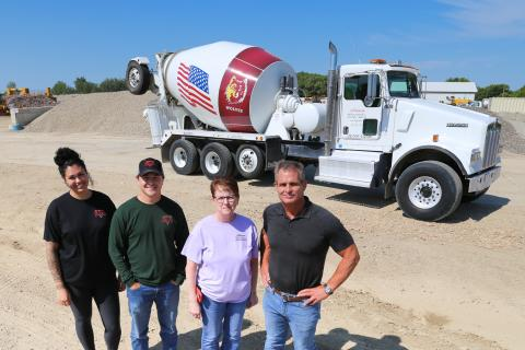 Four people standing in front of a cement truck