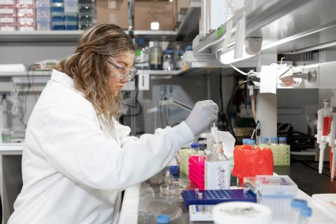 Young woman in white lab coat working in a science lab