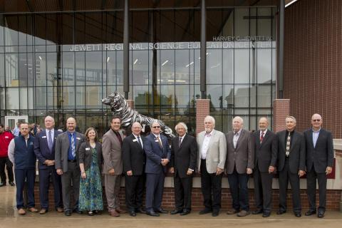 Several officials standing in front of the wolf sculpture at the Regional Science Education Center