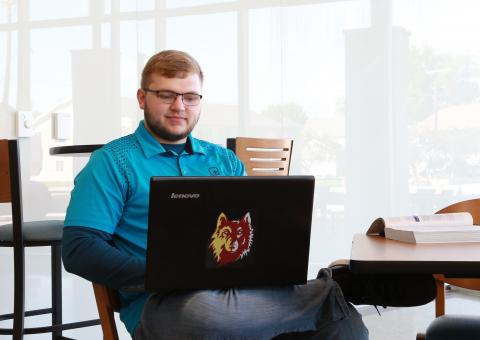 Male student seated with laptop