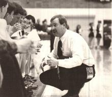 Photo of basketball coach talking to players