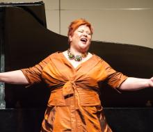 Female faculty member singing in front of piano