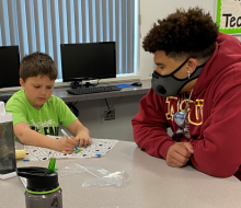 College student helping child at craft project