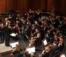 Symphony performing on stage led by conductor