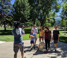 Family walking on campus being filmed by TV camera crew