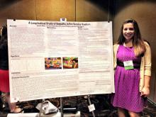 Female student standing by research poster