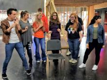 Group of theater students rehearsing together around a chair on stage