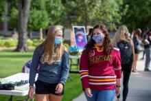 Students wearing masks walking on campus