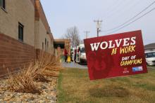 Day of Champions sign with students loading bus in background