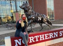 student sitting by wolf statue