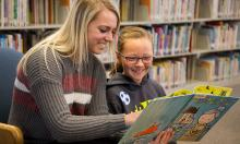 NSU student reading to elementary student