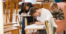 An NSU student bends over his drawing