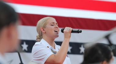 Female soldier singing in front of an American flag